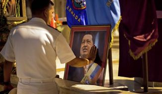 ** FILE ** In this Thursday, Dec. 13, 2012 photo, a member of Venezuela's navy touches an image of Venezuela's President Hugo Chavez after a mass in support of him in Havana, Cuba. Venezuelan Vice President Nicolas Maduro said late Monday, Dec. 24, 2012 night that he had spoken by telephone with Chavez and that the leader is up and walking following cancer surgery in Cuba. (AP Photo/Ramon Espinosa)