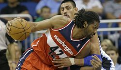 Washington Wizards' Nene (42), of Brazil, drives the ball around Orlando Magic's Gustavo Ayon, of Mexico, during the second half of an NBA basketball game on Wednesday, Dec. 19, 2012, in Orlando, Fla. Orlando won the game 90-83.(AP Photo/John Raoux)