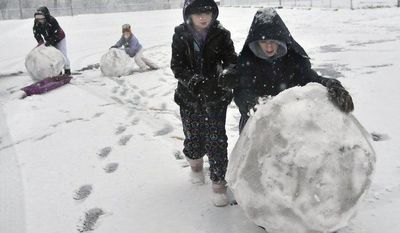 Hailey Greene (from left), 12, Joey Greene, 6, Carly Greene, 10, and Tyler Greene, 14, make a snowman on Monday, Dec. 24, 2012, as a Christmas Eve snowstorm blows through Martinsburg, W.Va. (AP Photo/Journal Newspaper, Ron Agnir)