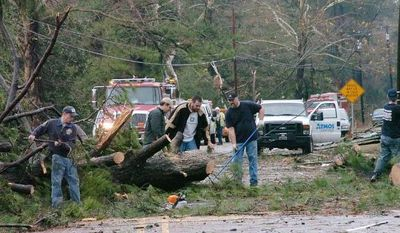 Members of the Alpine Volunteer Fire Department and the VA Fire Department clear debris from U.S. 71 in the Tioga, La. area, after an apparent tornado tore through the area Tuesday, Dec. 25, 2012. (AP Photo/The Daily Town Talk, Melinda Martinez)