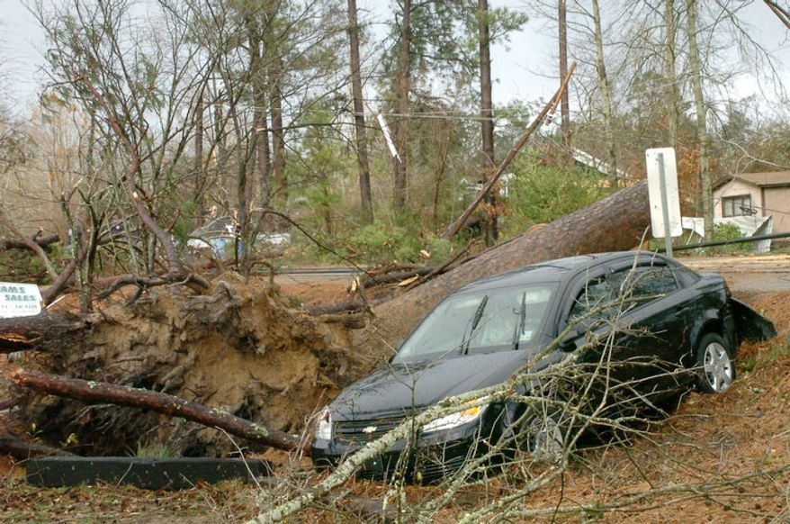 Geraldine Pedersen and her dog Marlow were in her car traveling down U.S. 71 in the Tioga, Louisiana area when a tree fell down in front of the car and a wind knocked her car into a yard, Tuesday, Dec. 25, 2012. A tornado through the Central Louisiana area. (AP Photo/The Town Talk, Melinda Martinez)