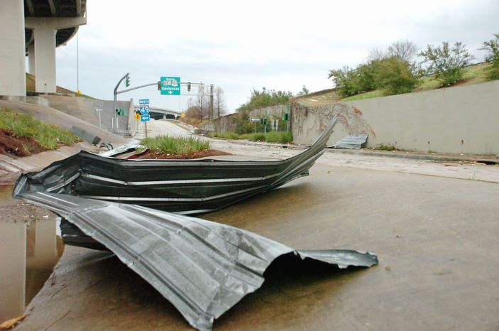 Debris sits on the frontage road near I-49 in downtown Alexandria, La., after an apparent tornado tore through the area Tuesday, Dec. 25, 2012. (AP Photo/The Daily Town Talk, Melinda Martinez)