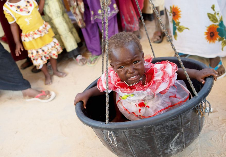 A little girl cries as she is weighed in a mobile nutrition clinic in Michemire, Chad. MIchemire is in a county that has one of the highest rates of stunting in the world. (Associated Press)