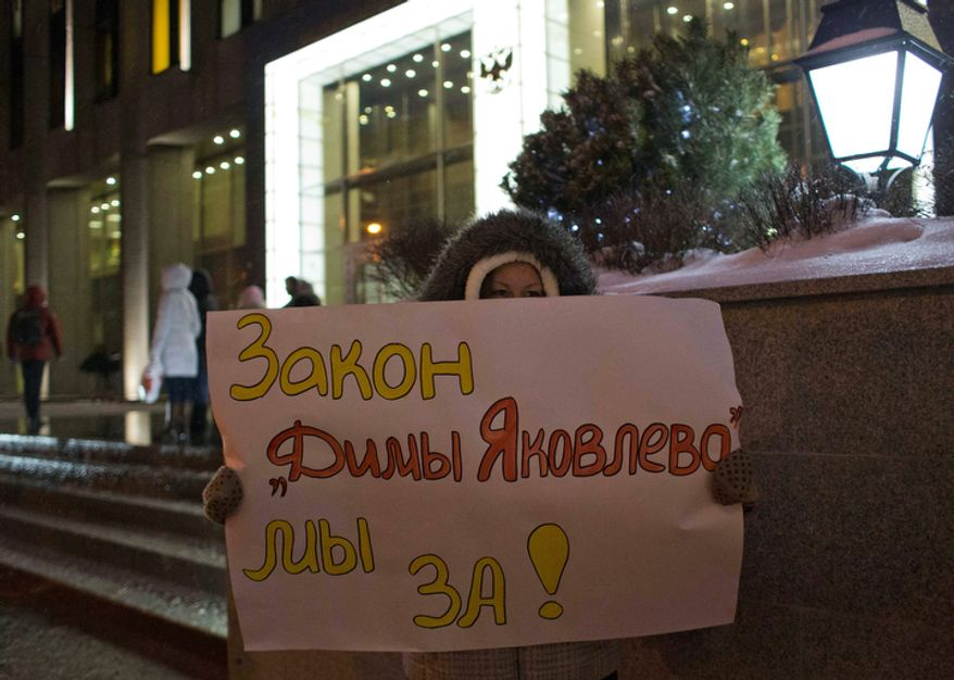 """A demonstrator holds a poster reading """"We are for Dima Yakovlev Bill"""" outside the Federation Council on Dec. 26, 2012. Several protesters were detained that morning outside the upper chamber of Russia's parliament as it prepared to vote on a controversial measure banning Americans from adopting Russian children. (Associated Press)"""