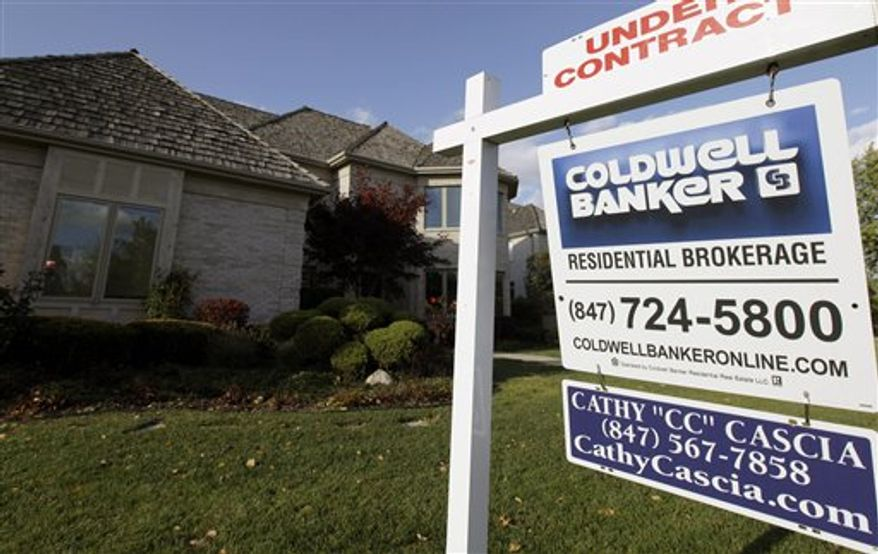 """An """"under contract"""" sign sits outside a home in Glen, Ill., on Wednesday, Oct. 10, 2012. (Associated Press)"""