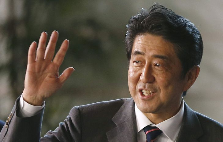 Japan's newly-named Prime Minister Shinzo Abe smiles as he waves at the media upon his arrival at the prime minister's official residence following his election at Parliament in Tokyo Wednesday, Dec. 26, 2012. Abe, whose nationalist positions have in the past angered Japan's neighbors, is the country's seventh prime minister in just over six years. (AP Photo/Shizuo Kambayashi)