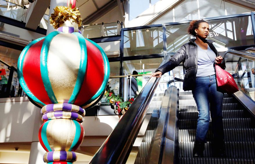 A woman rides the escalator past a giant holiday ornament at the CambridgeSide Galleria mall in Cambridge, Mass., Monday, Dec. 24, 2012.  (AP Photo/Michael Dwyer)