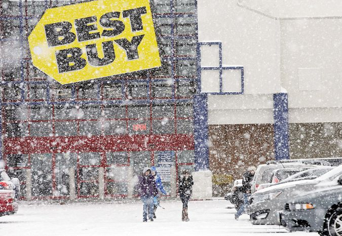 People walk in the parking lot of a Best Buy store during a severe snow storm in North Olmsted, Ohio Wednesday, Dec. 26, 2012. (