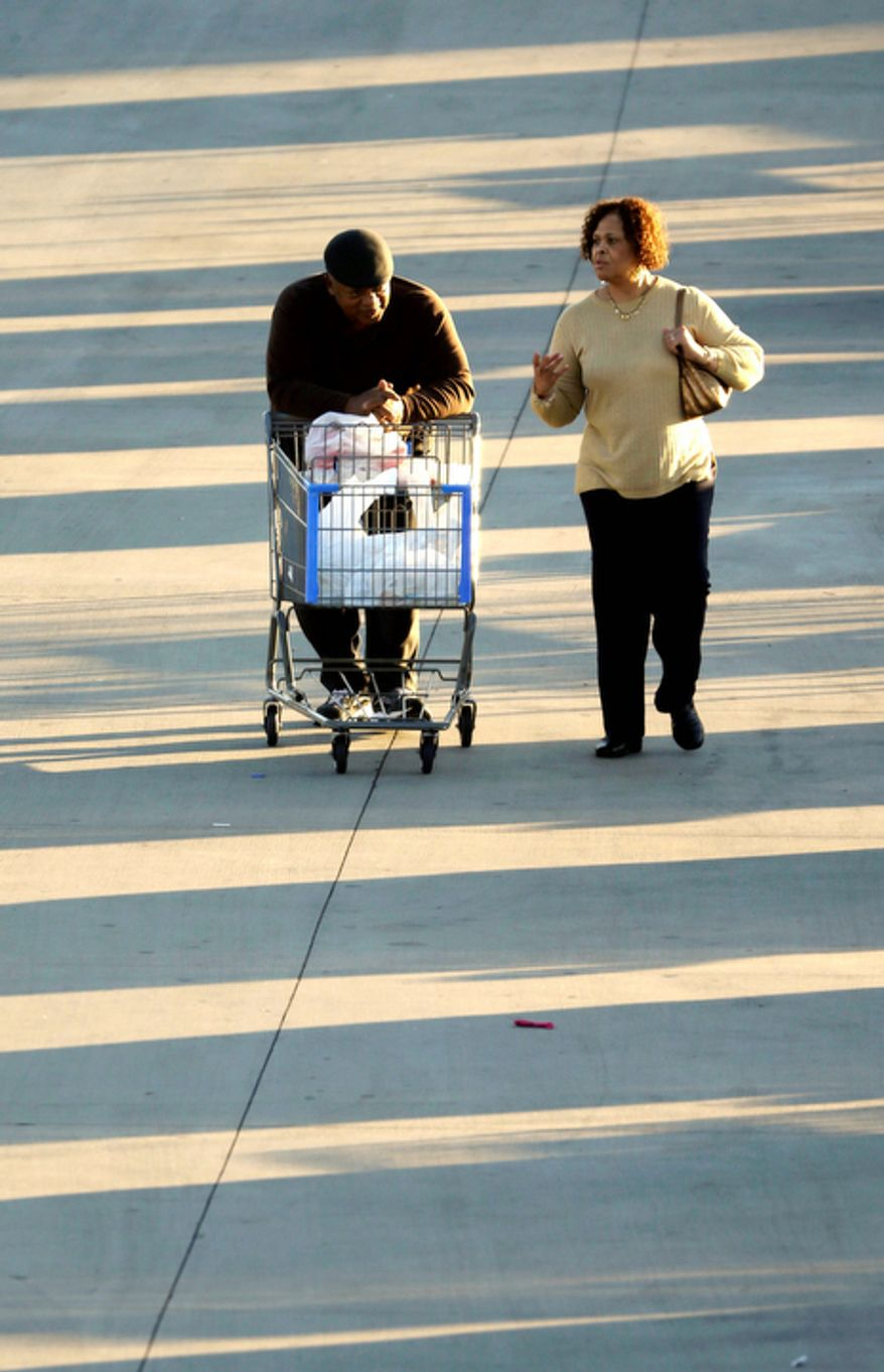 In this Tuesday, Dec. 18, 2012, file photo, shoppers push a cart with merchandise at a Walmart Supercenter store in Little Rock, Ark. U.S. holiday retail sales this year are the weakest since 2008, after a shopping season disrupted by storms and rising uncertainty among consumers.   (AP Photo/Danny Johnston)