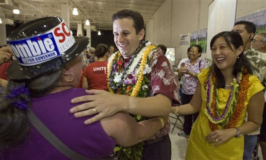 ** FILE ** In this Nov. 3, 2010 photo, a supporter congratulates then-Lt. governor-elect Brian Schatz, center, as his wife Linda looks on at the Neil Abercrombie-Brian Schatz Hawaii governor's post election party in Honolulu. Schatz was appointed by Gov. Abercrombie Wednesday, Dec. 26, 2012 to succeed the late U.S. Sen. Daniel Inouye. (Associated Press)