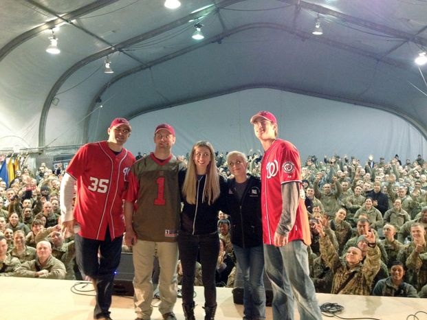 Washington Nationals player Craig Stammen, far left, Washington Capitals player Matt Hendricks, second left and Washington Nationals player Ross Detwiler, far right, pose with unidentified people during a USO tour.  (Co