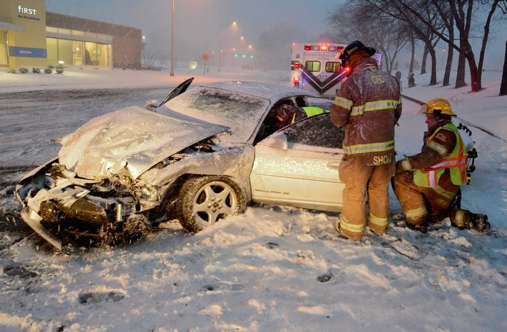 Rescuers work to move a driver injured in a wreck on a slick, snow-covered street in Columbus, Ind., Wednesday, Dec. 26, 2012. The blizzard warning issued the day before by National Weather Service came to fruition in the region Wednesday as winds picked up and snow began falling in earnest before dawn. (AP Photo/The Republic, Joe Harpring)