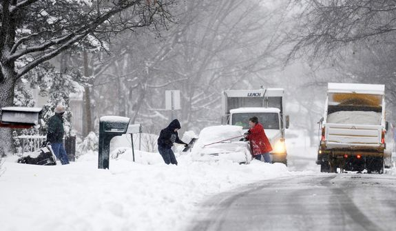 Residents clear cars and driveways as plows clear the streets in Carbondale, Ill. on Wednesday, Dec. 26, 2012. A gusty winter storm slammed southern Illinois on Wednesday, leaving roads covered in ice and snow and prompting authorities to warn of whiteout conditions that could significantly reduce drivers' visibility. (AP Photo/ The Southern Illinoisan, Aaron Eisenhauer)