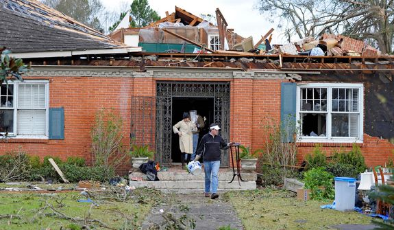 Tim Clarke, in black jacket, carries antiques from the the damaged home of family friend Anne Zieman (not pictured) as residents clean up and assess the damage from a Christmas Day tornado Wednesday, Dec. 26, 2012  in Mobile, Ala.  (AP Photo/G.M. Andrews)