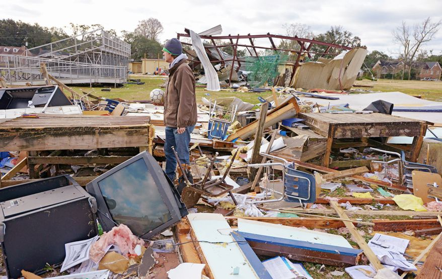 Murphy High School teacher Leland Howard tries to salvage items where his algebra classroom once stood in a temporary building at Murphy High School as residents clean up and assess the damage from a Christmas Day tornado Wednesday, Dec. 26, 2012  in Mobile, Ala.  (AP Photo/G.M. Andrews)