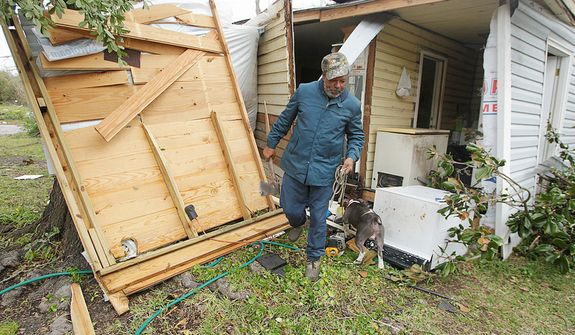 "Semler Street resident Mack Robinson checks on his tornado damaged home Wednesday, Dec. 26, 2012, in Prichard, Ala. Robinson's wife, Mary, was home when the tornado hit. ""Nobody got hurt, except my feelings,"" Robinson said. (AP Photo/AL.com, Mike Kittrell)  MAGS OUT"