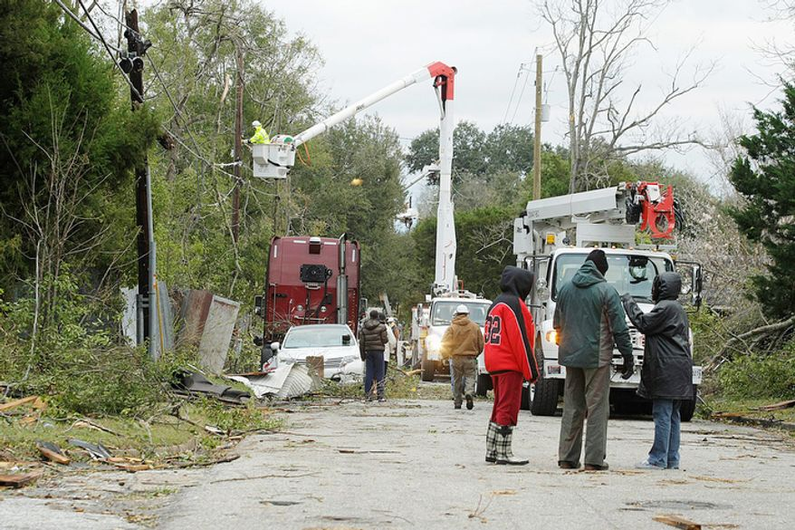 Utility crews work to restore powe in Mobile, Ala., Wednesday, Dec. 26, 2012, after a tornado swept through the area on Christmas Day. With only a handful of injuries and no deaths reported statewide from the storms, the head of the state's emergency response said it was difficult to fathom how the toll wasn't worse. (AP Photo/AL.com, Mike Kittrell)