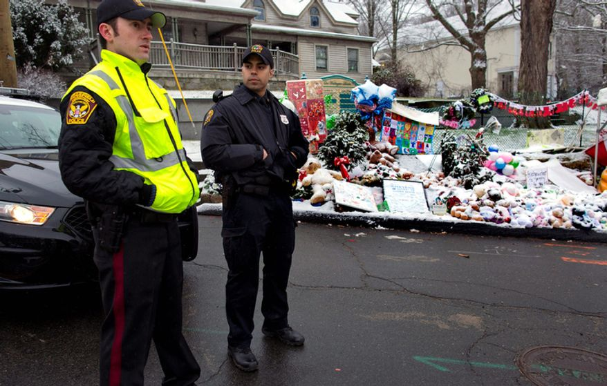 From left, Town of Ridgefield, Conn., Det. Durling, and Town of Greenwich, Conn., Officer Rivera stand near a memorial in Newtown, Conn. Tuesday, Dec. 25, 2012. Regional police agencies arrived in Newtown to relieve the local police force for the Christmas holiday. (AP Photo/Craig Ruttle)
