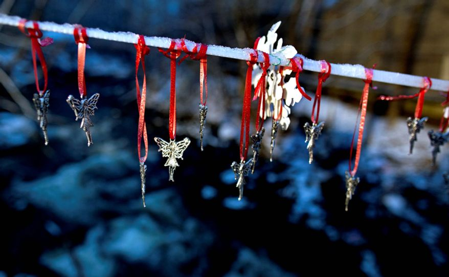 Angel pendants hang from a snow-covered string in Newtown, Conn. Tuesday, Dec. 25, 2012. People continue to visit memorials in the wake of the shootings after gunman Adam Lanza walked into Sandy Hook Elementary School in Newtown, Conn., Dec. 14, and opened fire, killing 26, including 20 children, before killing himself.  (AP Photo/Craig Ruttle)