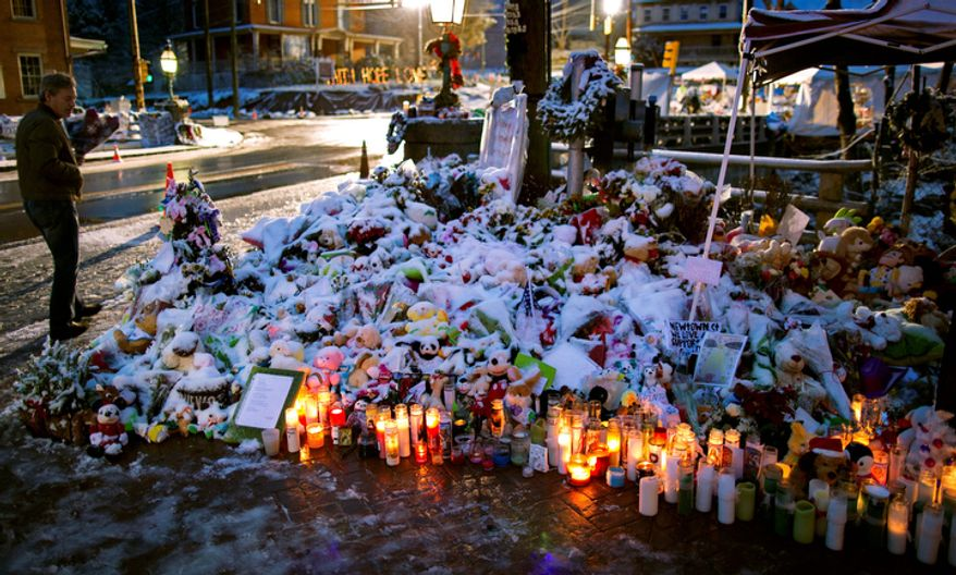 A member of the Rutter family of Sandy Hook, Conn., walks past candles and other offerings that make up a memorial in Newtown, Conn., Tuesday, Dec. 25, 2012. People continue to visit memorials  after gunman Adam Lanza walked into Sandy Hook Elementary School in Newtown, Friday, Dec. 14, and opened fire, killing 26, including 20 children, before killing himself. (AP Photo/Craig Ruttle)