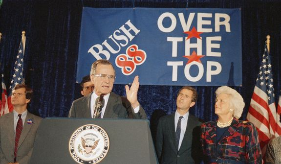Vice President George H. W. Bush, second from left, with his wife Barbara Bush, looking on at right, addresses supporters during an Over the Top rally, Tuesday, May 4, 1988, Washington, D.C. Bush, who clinched the Republican presidential nomination last week, waited until Tuesday to celebrate his success and wins in uncontested Indiana, Ohio and the District of Columbia primary races. Bush's son, George W. Bush is second from right. The man on the left is unidentified. (AP Photo/Charles Tasnadi)