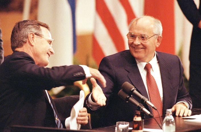 U.S. President George Bush shakes hands with Soviet President Mikhail Gorbachev at the conclusion of their joint news conference ending the one day summit, Sunday, Sept. 9, 1990 in Helsinki. (AP Photo/Liu Heung Shin)