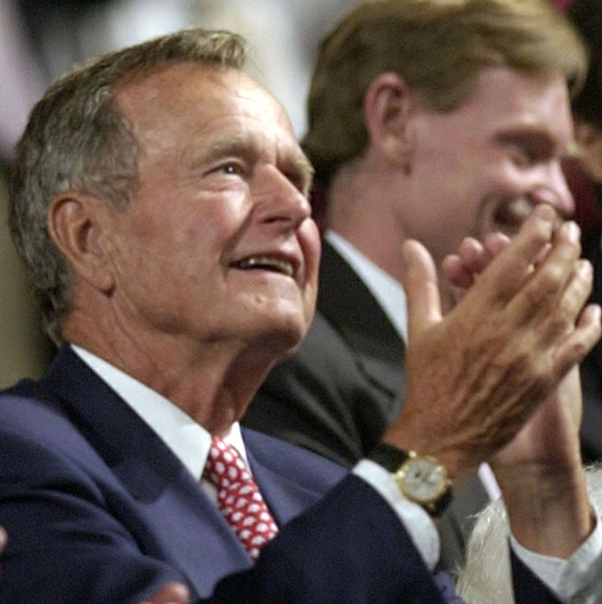 Former President George H. W. Bush applauds during the evening session of  the first day of the Republican National Convention Monday, Aug. 30, 2004, in New York. (AP Photo/Charlie Riedel)