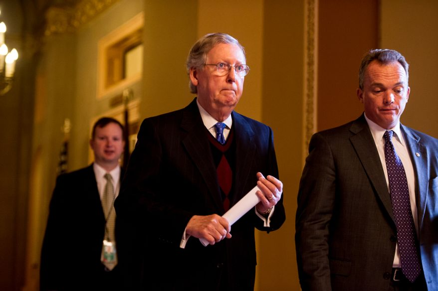 Senate Minority Leader Mitch McConnell (center), Kentucky Republican, makes his way to the U.S. Senate floor at the U.S. Capitol Building in Washington on Dec. 27, 2012. (Andrew Harnik/The Washington Times)