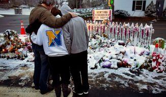 Members of the Rutter family of Sandy Hook, Conn., embrace early on Christmas morning, Tuesday, Dec. 25, 2012, as they visit memorials to shooting victims near the Sandy Hook firehouse in Newtown, Conn. (AP Photo/Craig Ruttle)
