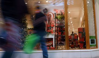 Christmas shoppers walk past a store at a mall in Salem, N.H., on Friday, Dec. 21, 2012. (AP Photo/Elise Amendola)