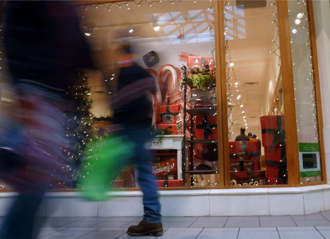 Christmas shoppers walk past a store at a mall in Salem, N.H., on Friday, Dec. 21, 2012. (AP Ph