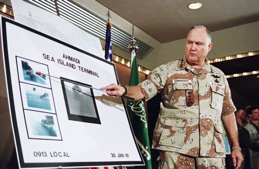 **FILE** U.S. Army Gen. Norman Schwarzkopf points Jan. 27, 1991, to a row of photos of Kuwait's Ahmadi Sea Island Terminal on fire after a U.S. attack on the facility. (Associated Press)