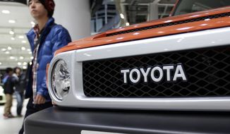 A visitor walks past a car at a Toyota showroom in Tokyo, Thursday, Dec. 27, 2012. Toyota Motor Corp. said it has reached a settlement worth more than $1 billion in a case involving unintended acceleration problems in its vehicles. (AP Photo/Shizuo Kambayashi)