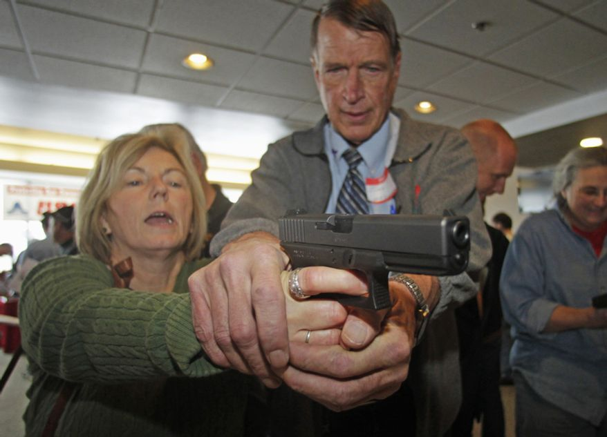 Christine Caldwell (left) receives firearms training with a 9mm Glock from personal defense instructor Jim McCarthy on Dec. 27, 2012, during concealed-weapons training for 200 Utah teachers in West Valley City, Utah. The Utah Shooting Sports Council offered six hours of training in handling concealed weapons in the latest effort to arm teachers to confront school assailants. (Associated Press)