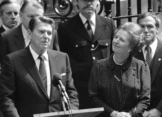 **FILE** Britain's Prime Minister Margaret Thatcher smiles with satisfaction as President Ronald Reagan makes a farewell speech June 9, 1982, outside her Downing Street office in London prior to his departure for Bonn. (Associated Press)