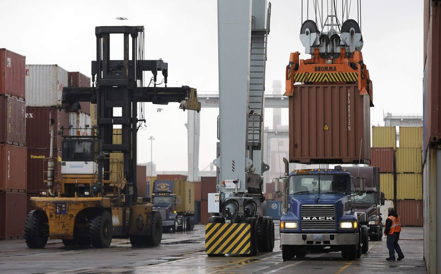 ** FILE ** In this Dec. 18, 2012, file photo, a truck driver watches as a freight container, right, is lowered onto a tractor trailer by a container crane at the Port of Boston in Boston. The crane and a reach stacker, left, are operated by longshoremen at the port. (AP Photo/Steven Senne, File)