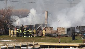 **FILE** Firefighters gather around a burning house after they were let back into the area to battle the blaze on Dec. 24, 2012, in Webster, N.Y. A gunman ambushed four volunteer firefighters responding to the fire, killing two and ending up dead himself, authorities said. (Associated Press/Democrat & Chronicle)