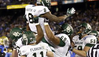 Baylor running back Glasco Martin is lifted by teammates after scoring a touchdown against UCLA during the first half of Baylor's 49-26 win in the Holiday Bowl on Dec. 27, 2012, in San Diego. (Associated Press)