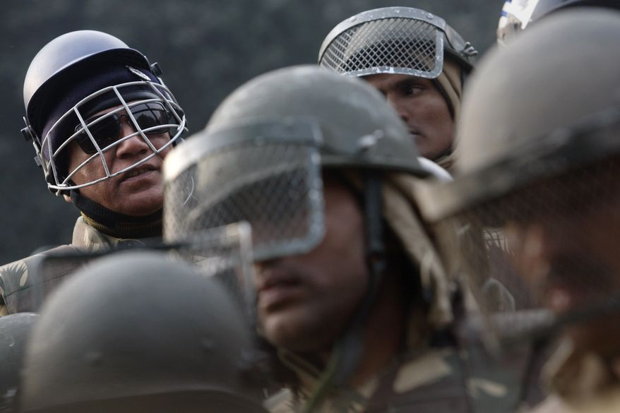 An Indian police officer (left) sports a cricket helmet Dec. 27, 2012, as fellow policemen stand near barricades and stop protesters on their way to India Gate while protesting against a gang-rape of a young woman in a moving bus in New Delhi. (Associated Press)