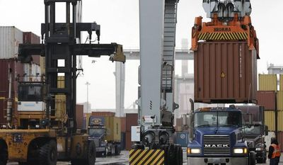 **FILE** A truck driver watches as a freight container is lowered onto a tractor trailer by a container crane at the Port of Boston in Boston on Dec. 18, 2012. The crane and a reach stacker at left are operated by longshoremen at the port. (Associated Press)