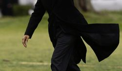 President Obama waves as he steps off the Marine One helicopter and walks on the South Lawn at the White House in Washington on Dec. 27, 2012, as he returned early from his Hawaii vacation for meetings on the fiscal cliff. (Associated Press)