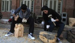 **FILE** Pakistani students carve wooden statues in the National College of Arts in Lahore, Pakistan, on Dec. 6, 2012. (Associated Press)