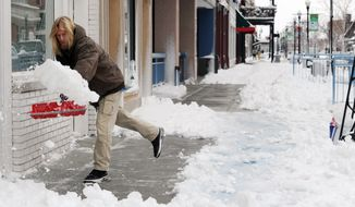 Scott Becker shovels the sidewalks of businesses along Main Street in downtown Evansville, Ind., on Dec. 27, 2012. (Associated Press/The Evansville Courier & Press)