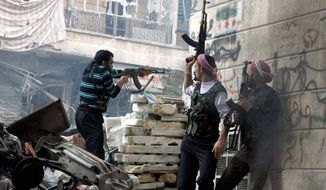 Free Syrian Army fighters fire at enemy positions during clashes with government forces in the Salaheddine district of Aleppo on Saturday. A U.N. envoy warns 100,000 Syrians could be killed next year if fighting continues. (Associated Press)
