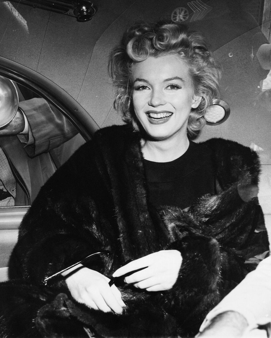** FILE ** In this June 2, unknown year, file photo, actress Marilyn Monroe smiles in a car after arriving tousled from an all-night plane flight from Hollywood to Idlewild Airport, in New York. (AP Photo, File)
