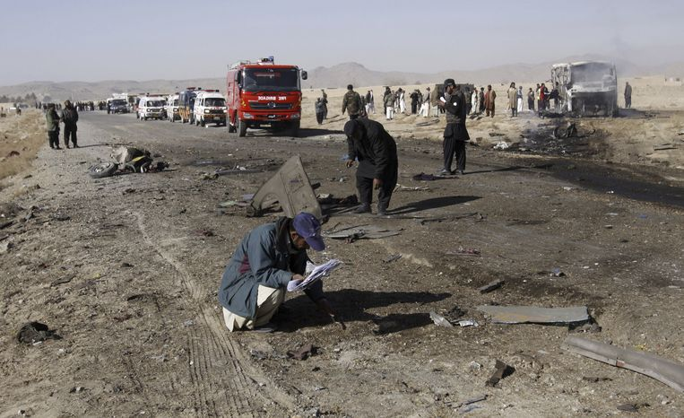 Pakistani police officers collect evidence from the site of a suicide bombing in Quetta, Pakistan, on Sunday, Dec. 30, 2012. A suicide bomber driving a pickup truck packed with explosives rammed into a bus carrying Shiite Muslim pilgrims in the country's southwest, killing 19 people, a government official and eyewitnesses said. (AP Photo/Arshad Butt)