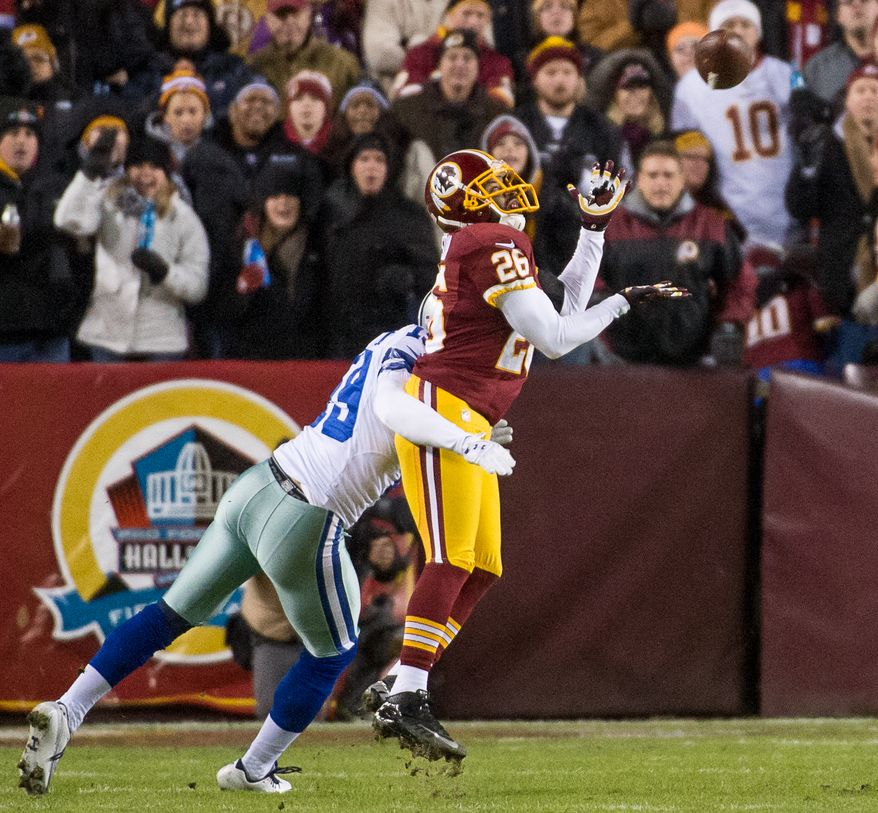 Washington Redskins cornerback Josh Wilson (26) intercepts a ball intended for Dallas Cowboys wide receiver Miles Austin (19) in the first quarter as the Washington Redskins play the Dallas Cowboys at FedEx Field, Landover, Md., Sunday, December 30, 2012. (Andrew Harnik/The Washington Times)