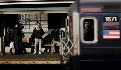 Commuters watch as a train enters the 40th Street-Lowry Street Station, where a man was killed after being pushed onto the subway tracks, in the Queens borough of New York on Friday, Dec. 28, 2012. (AP Photo/Seth Wenig)