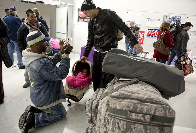 James Brennan of Philadelphia, Penn. kneels down to get video footage of his 10-month-old granddaughter Christina, who just got off the plane with dad Christopher on a military charter flight at BWI Thurgood Marshall Airport on Friday, Dec. 28, 2012. This was Brennan's first time seeing his granddaughter. She was one of about 300 people on the charter flight, which brought troops and military contractors back to the United States. (Barbara L. Salisbury/The Washington Times)