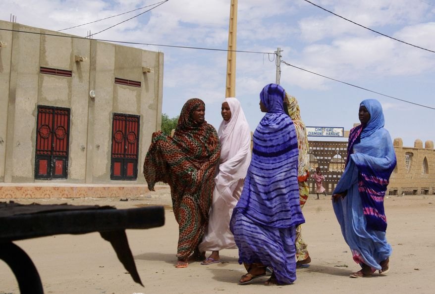 **FILE** Women wearing veils, as mandated by Islamist group Ansar Dine, walk along a street in Timbuktu, Mali, on Oct. 18, 2012. (Associated Press